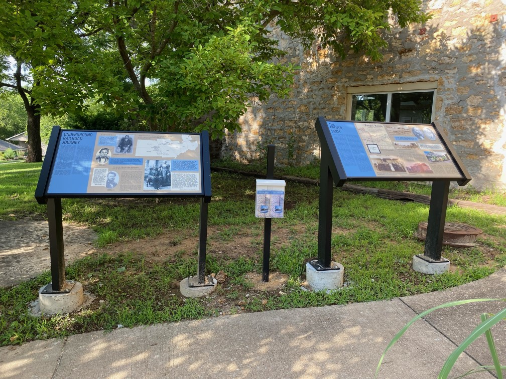 Two informational kiosks in front of the Grover Barn with a brochure holder between them.